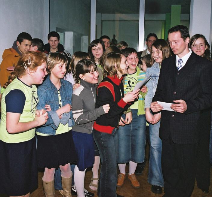 """Tomasz Jezuit, dyrygent """"Corda Vox"""" z Terespola w otoczeniu młodzieży ze swojego zespołu"""